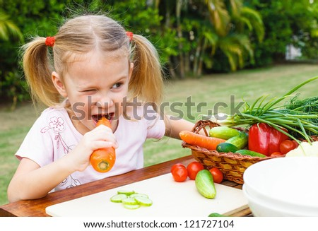 Happy little girl holding a carrots. Concept of healthy food. - stock photo