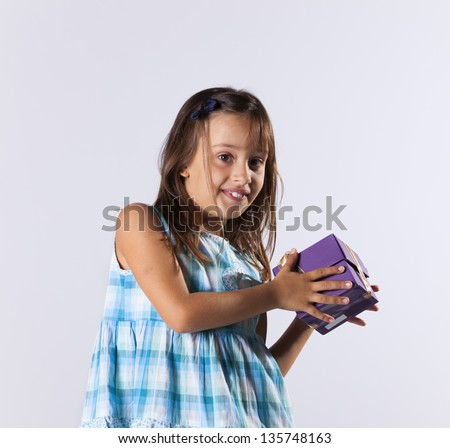 Happy little girl holding a gift box