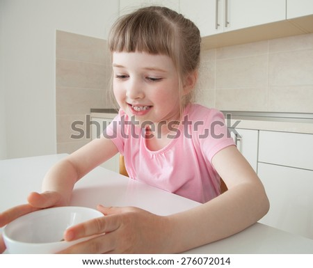 Happy little girl holding a white bowl at home - stock photo