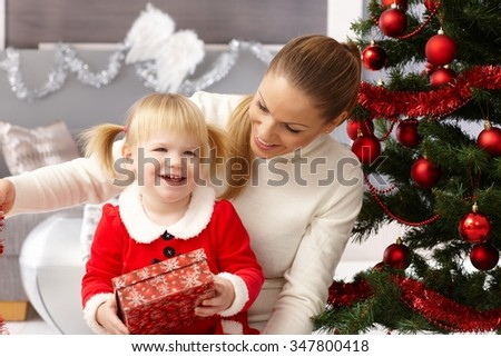Happy little girl holding christmas present, sitting on mothers' lap by christmas tree.