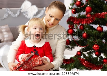 Happy little girl holding christmas surprise sitting by christmas tree with mother. - stock photo