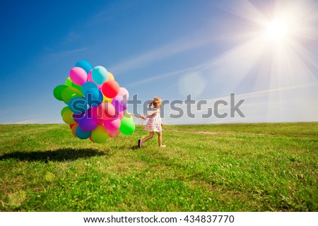 Happy little girl holding colorful balloons. Child playing on a green meadow. Smiling kid.  - stock photo