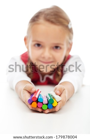 Happy little girl holding colorful modelling clay bars - shallow depth