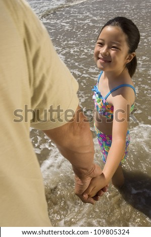 Happy little girl holding father's hand on beach - stock photo