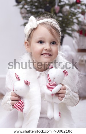 Happy little girl holding handmade toys with christmas tree in background.