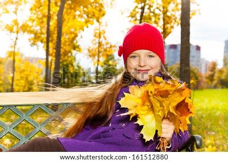 Happy little girl holding maple leaves bouquet sitting on the bench in autumn park