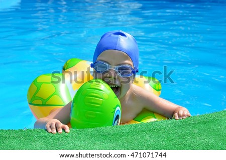 Happy little girl holding pool overboard. A child wearing a hat and sunglasses for seamlessly for a smooth, in the pool.