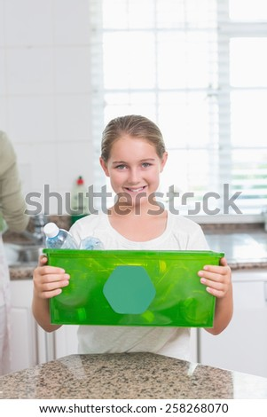 Happy little girl holding recycling box at home in the kitchen - stock photo