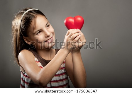 happy little girl holding red heart