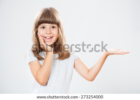 Happy little girl holding your message or product