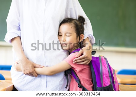 happy little Girl hugging her mother in classroom - stock photo