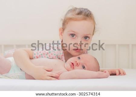Happy little girl hugging her newborn brother - stock photo
