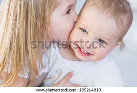 happy little girl hugging kissing his brother - stock photo
