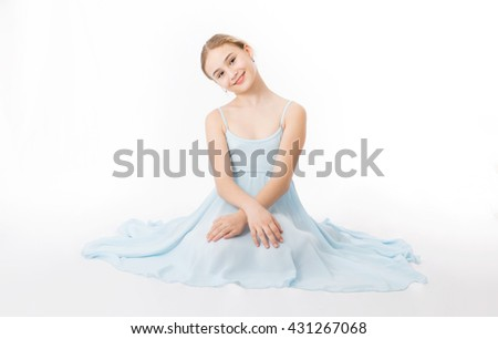 Happy little girl in a blue dress is sitting on the floor on a white background - stock photo