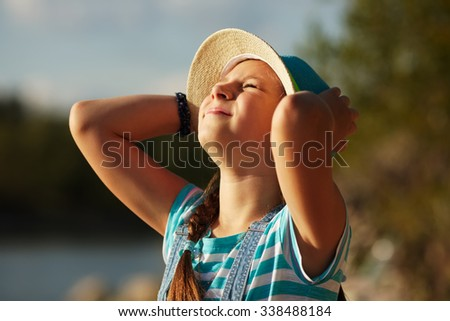 Happy little girl in a hat squinting from the sun - stock photo