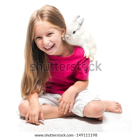 happy little girl in a pink T-shirt with a small white rabbit - stock photo