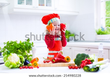 Happy little girl in a red chef hat and apron preparing healthy lunch with fresh raw vegetables, making salad with tomato, eggplant, pepper and cauliflower in a white kitchen at home - stock photo