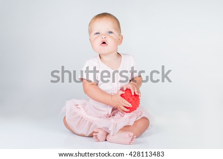 Happy little girl in a short pink dress throws a big striped ball