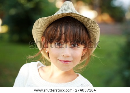 Happy little girl in a straw hat - stock photo