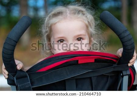 happy little girl in a stroller playfully peeking - stock photo