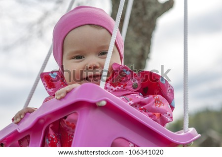 Happy little girl in a swing - stock photo