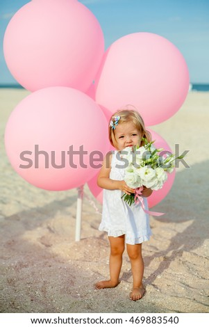 happy little girl in a white dress standing on the beach near the big balloons