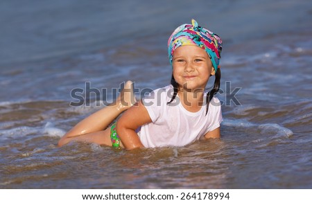Happy little girl in a white t-shirt and colorful bandana having fun in the water at the beach. - stock photo