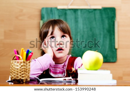 Happy little girl in classroom - stock photo