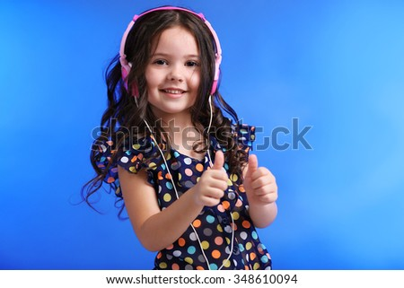 Happy little girl in colourful shirt with pink headphones on blue background - stock photo