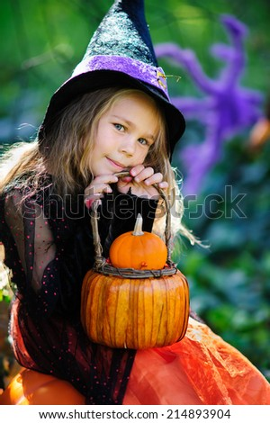 Happy little girl in halloween costume with jack pumpkin, tick or treat
