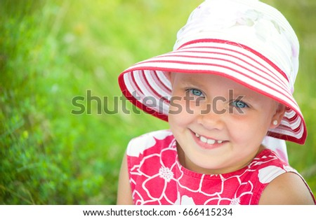 happy little girl in  hat smiling  on green grass