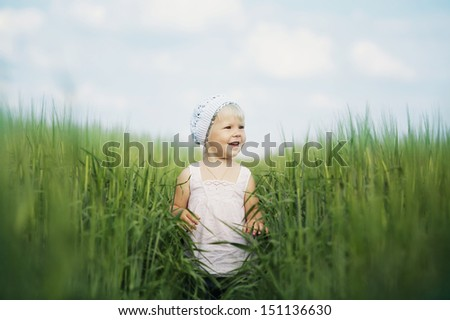 happy little girl in high grass - stock photo