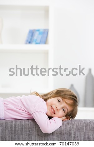 Happy little girl in pink dress, lying on couch, smiling.? - stock photo