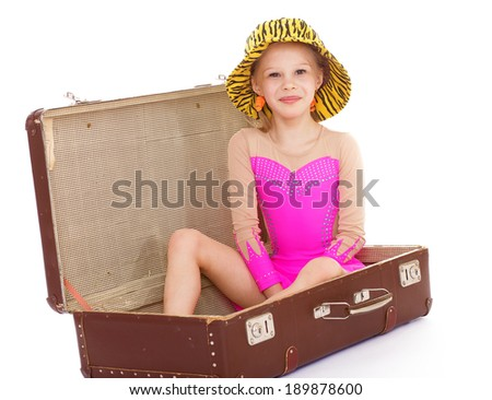 Happy little girl in retro outfit sitting on travel suitcase.Isolated on white background. - stock photo