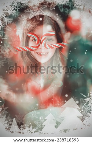 Happy little girl in santa hat holding candy canes against candle burning against festive background