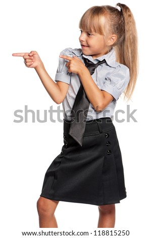 Happy little girl in school uniform showing something isolated on white background - stock photo