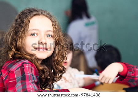 Happy little girl in school with her friends arround - stock photo