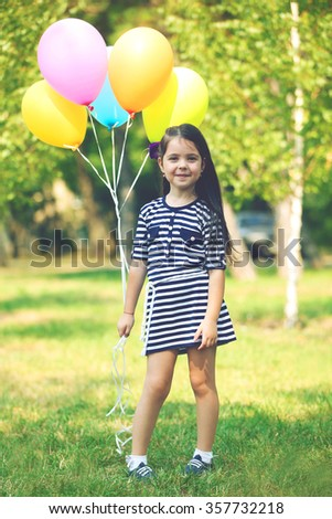 Happy little girl in striped dress with colourful balloons in the park