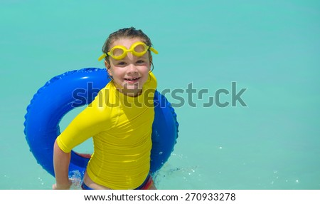 Happy little girl in swimming goggles with a floating ring at a tropical beach - stock photo