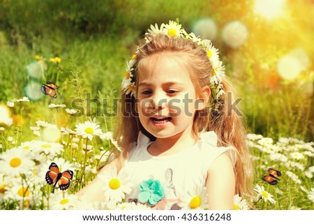 Happy little girl in the chamomile field in summer.