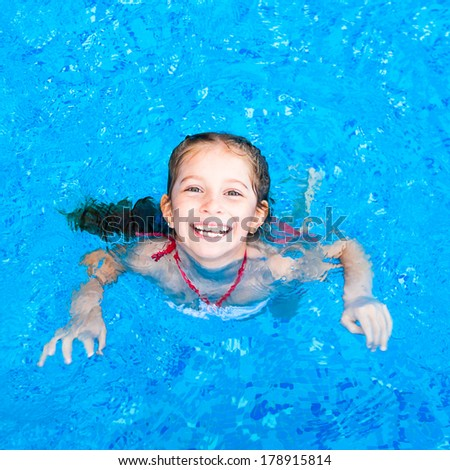 happy little girl in the pool - stock photo