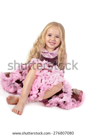 Happy little girl in tutu skirt sitting on the floor isolated on a white background - stock photo