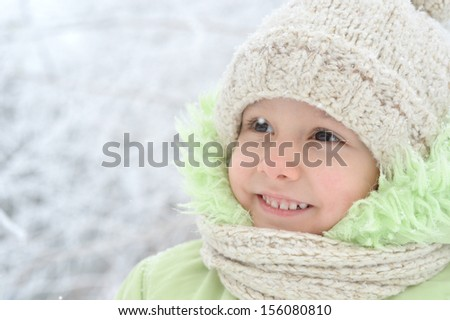 Happy little girl in warm clothes in winter outdoors - stock photo