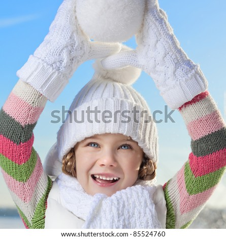happy little girl in warm clothing outdoors playing with snow ball - stock photo