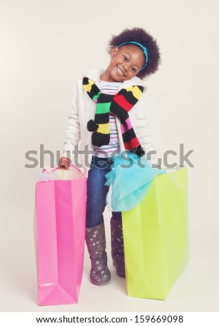 Happy little girl in winter attire with full shopping bags.  - stock photo