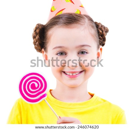 Happy little girl in yellow t-shirt and party hat holding colored candy - isolated on white. - stock photo