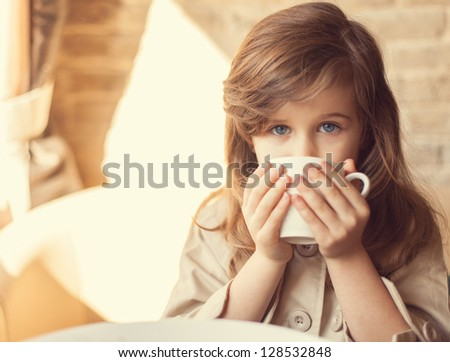 happy little girl indoors eating and smiling - stock photo