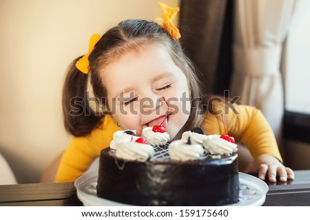 happy little girl indoors with a birthday cake - stock photo