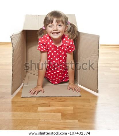 happy little girl inside a paper box - stock photo