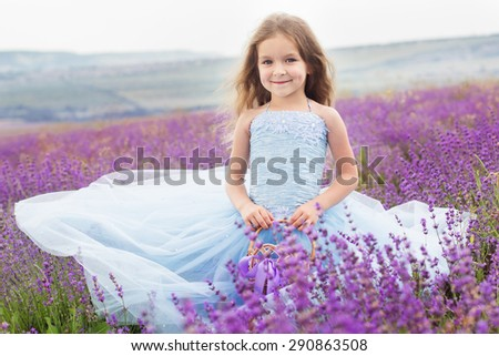 Happy little girl is in a lavender field holds a basket with ribbon - stock photo